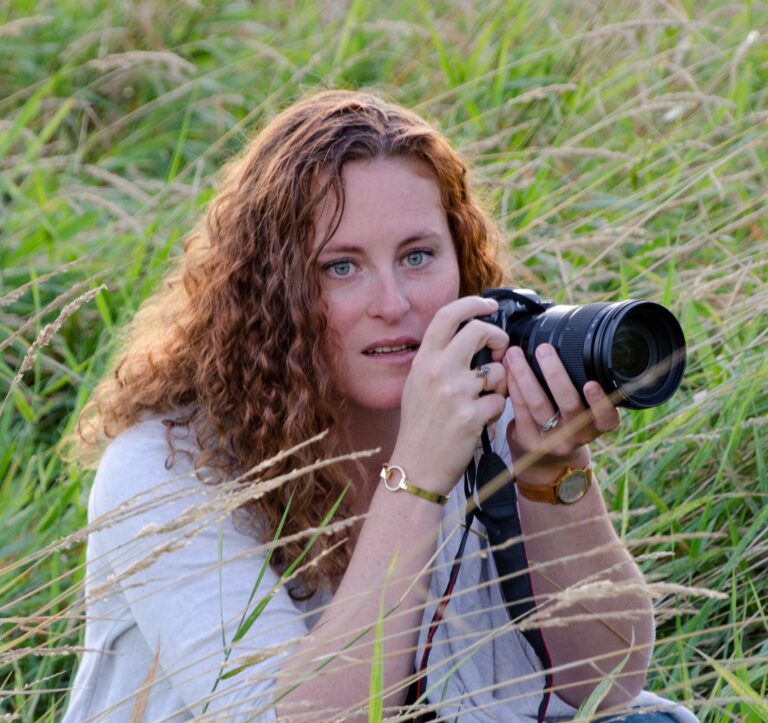 Erin Burrell holding camera in the middle of tall grass
