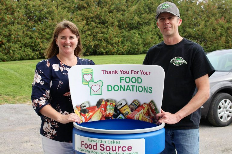Two people smiling standing beside a food donation barrel