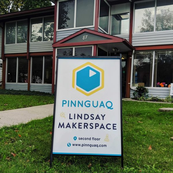 A Pinnguac sign on a lawn in front of a large building