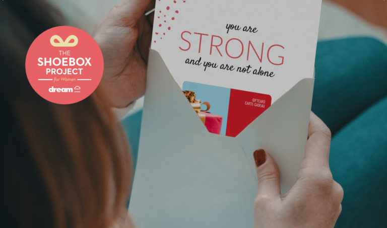 """A woman opening an envelope which has a gift card enclosed. A message on the gift card reads """"you are strong and you are not alone""""."""
