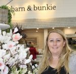 "A woman stands beside flowers. On the wall behind her, are the words ""barn and bunkie""."
